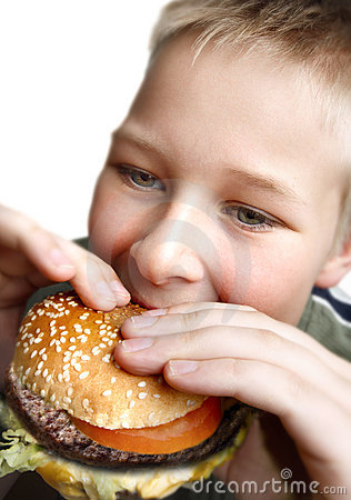 Young boy eating cheeseburger