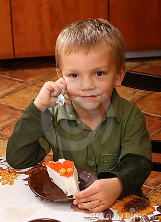 Young boy eating cheesecake