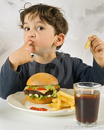 Young boy eating chessburger