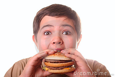 Young boy eating hamburger
