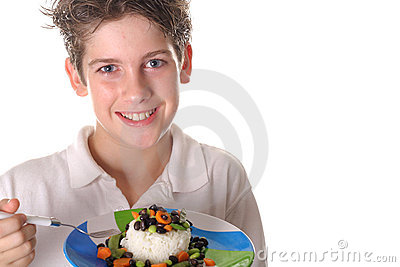 Young boy eating healthy rice, beans & veggies