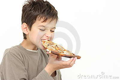 A young boy eating pizza
