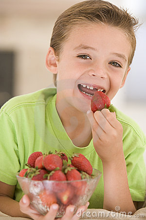 Young boy eating strawberries in living room