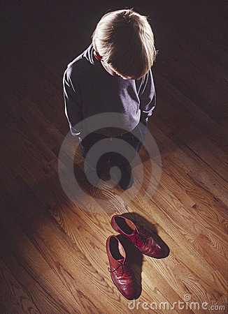 Young boy with father s shoes