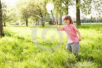 Young Boy In Field With Insect Net