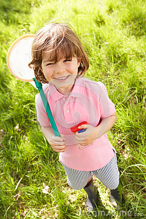 Young Boy In Field With Net And Bug Catcher