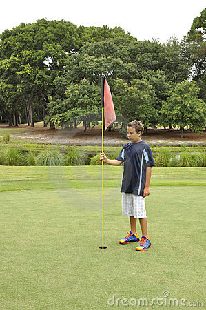 Young boy with flag on golf course