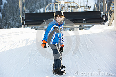Young Boy Getting Off Chair Lift On Ski Holiday
