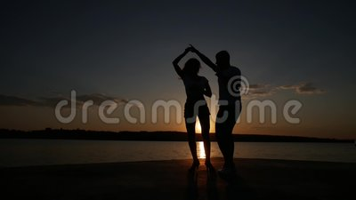 Young boy and girl dance salsa at sunset near the lake. Silhouette shooting. Slow motion.  stock footage