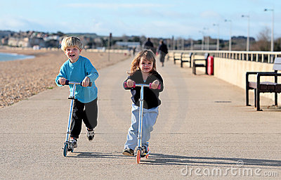 Young boy and girl playing on scooters