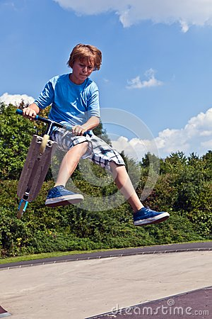 Young boy going airborne with his scooter