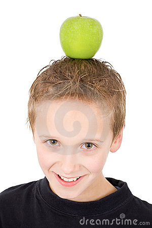 Young boy with a green apple on the head