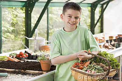 Young boy in greenhouse holding basket