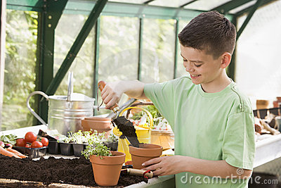 Young boy in greenhouse putting soil in pot