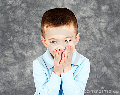 Young boy hiding face in hands
