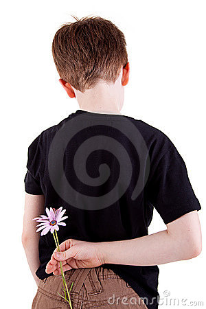 Young boy hiding flowers behind his back