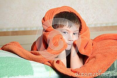 Young boy hiding under blanket