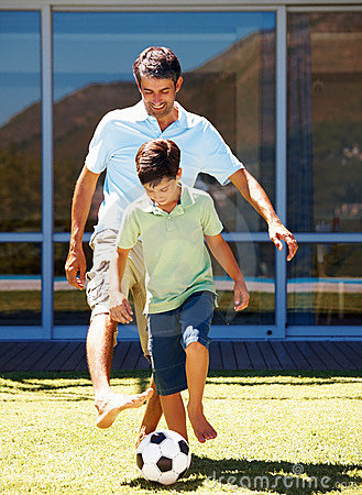 Young boy and his dad playing football