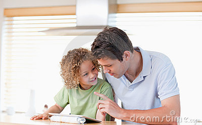 Young boy and his father using a tablet computer