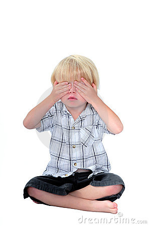 Young boy with his hands over his eyes and white background