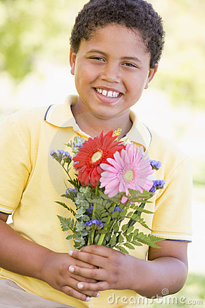 Young boy holding flowers