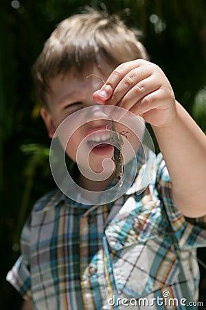 Young boy holding a lizard