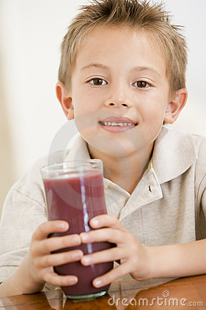 Young boy indoors drinking juice