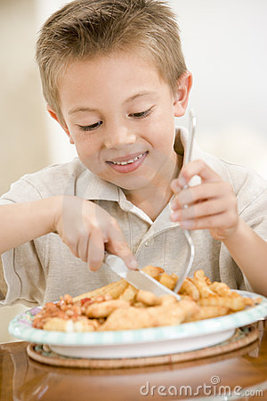 Young boy indoors eating fish and chips