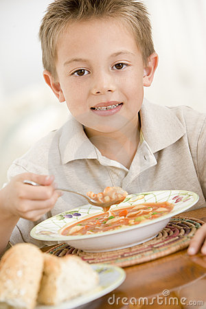 Young boy indoors eating soup