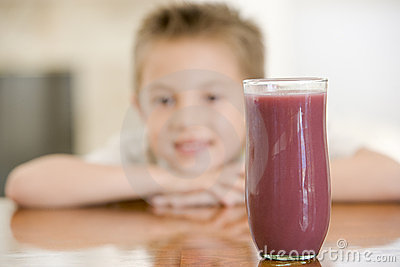 Young boy indoors with focus on juice glass