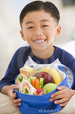 Young boy indoors with packed lunch
