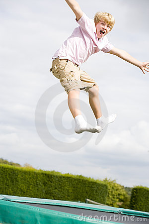 Young boy jumping on trampoline smiling