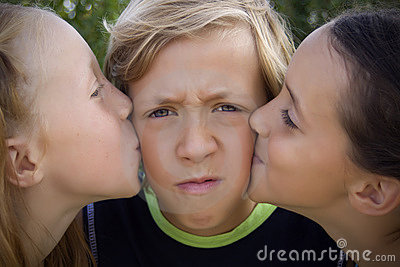Young boy kissed by two girls