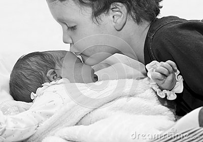 Young boy kissing baby sister