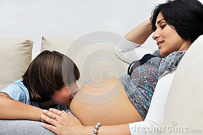 Young boy kissing pregnant woman