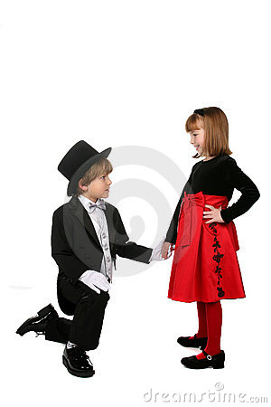 Young boy kneeling down and holding girl s hand