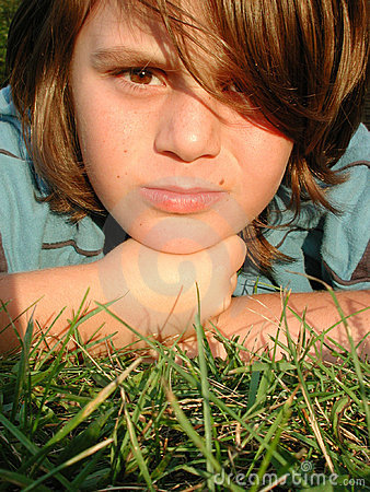 Young boy laying in grass