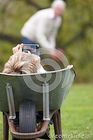 Young Boy Laying Wheelbarrow Using Mobile Phone