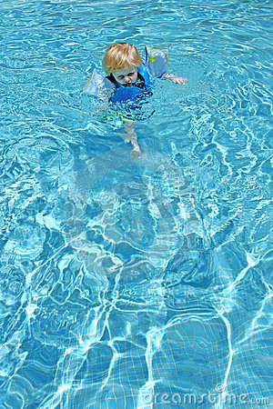 Young boy learning to swim in pool
