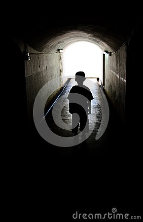 Young boy in long tunnel walkway