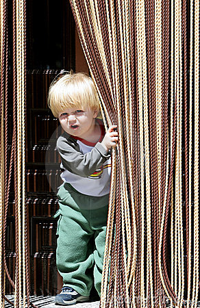 Free Young Boy Looking Out From Behind Curtain Royalty Free Stock Photos - 123798
