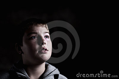 Young boy looking up with hope in his eyes Low key
