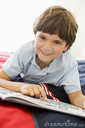 Young Boy Lying Down On His Bed Reading A Book