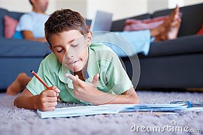 Young boy lying on the floor and doing homework