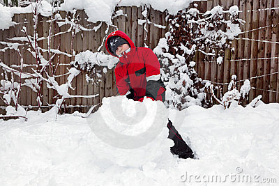 Young boy making a snowman