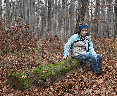 Young boy on old log in forest