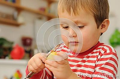 Young boy peeling potato