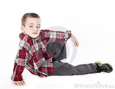 Young boy in plaid shirt laying on his side