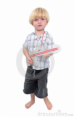 Young boy playing cardboard guitar with white background