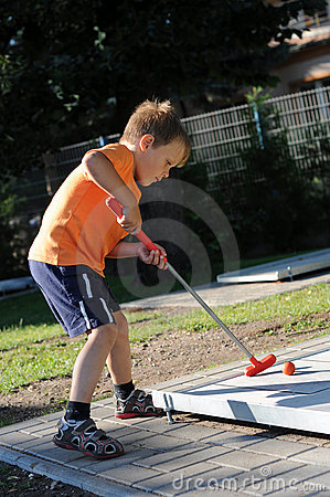 Young boy playing mini golf